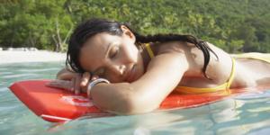 Young woman floating on bodyboard near beach