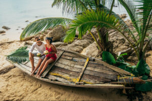 Happy couple sitting in boat on beachshore