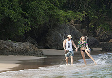 White couple holding hands on beach