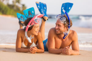 Young couple laughing while lying on beach