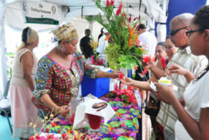 Woman serving guests from a booth at the Culinary Festival, Tobago
