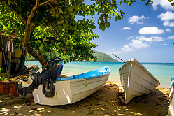 Two Pirogue boats on beach shore