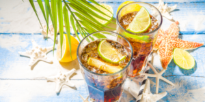 Cuba Libre, long island iced tea Caribbean cocktail with strong alcohol, cola, lime, crushed ice, tropical background with starfish, palm leaves
