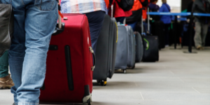 A line of travellers with suitcases in airport at the checkin counter