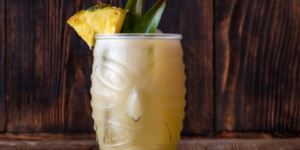 Glass of Painkiller cocktail on wooden background
