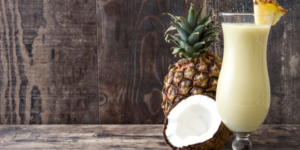 Pina Colada drink with pineapple and cut coconut on wood background