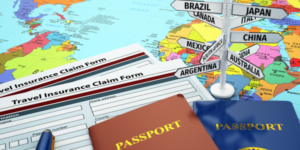 Travel insurance and two passports on top of a map with different world destinations
