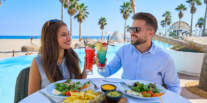 Couple sipping Caribbean cocktails and eating breakfast at beachside hotel restaurant