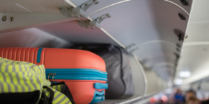 Hand luggage checked in overhead compartment on plane