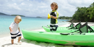 Young boy in bathing suit next to green canoes on the beach in St. John