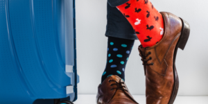 Man with wearing one red and blue sock next to a suitcase