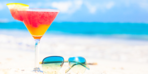 glass of chilled cocktail rum punch and sunglasses on table near the beach