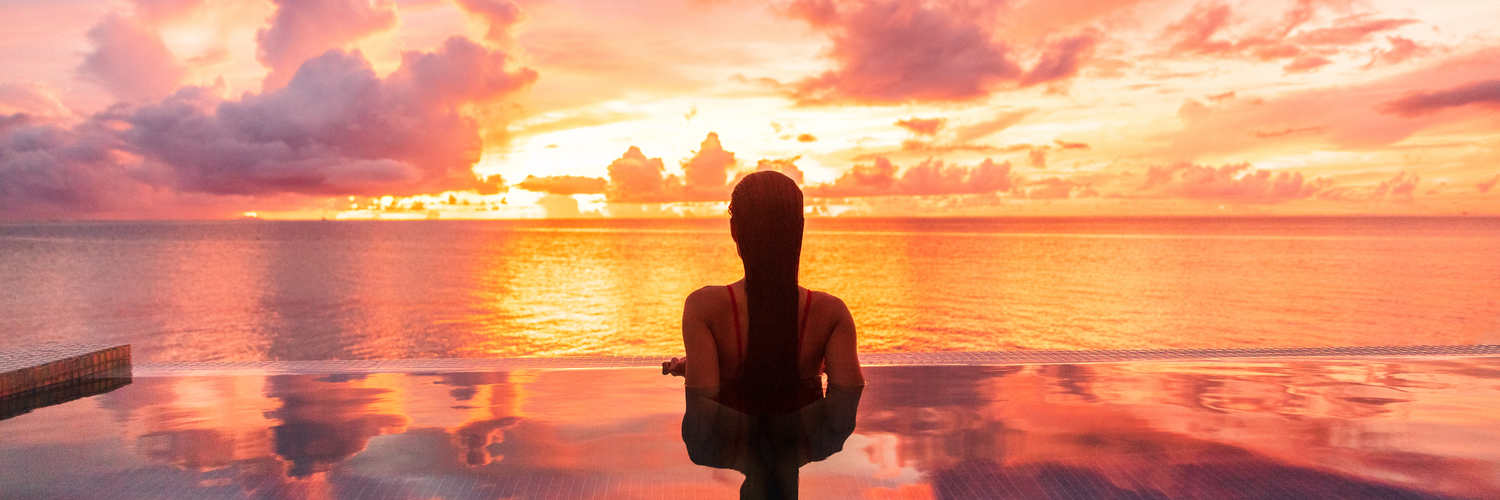 Young woman at infinity pool edge looking at sunset